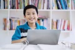 Azjatycki preteen uczeń używa laptop w bibliotece Obrazy Stock