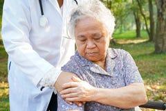 Azjatycki senior ostro?nie, starszy starej damy kobiety pacjent, pomoc lub poparcie na w?zku inwalidzkim w parku w wakacje, zdjęcie royalty free