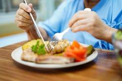 Azjatycki senior, starszego starej damy kobiety cierpliwego ?asowania ?niadaniowy zdrowy jedzenie z nadziej? lub szcz??liwy i zdjęcia royalty free