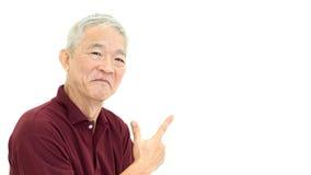 Azjatycki senior wskazuje ono uśmiecha się na bielu odizolowywa tło Obraz Royalty Free