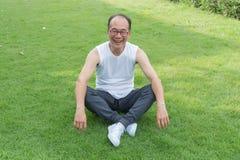 Azjatycki starego człowieka uśmiech i siedzi na trawie przy parkiem, relaksuje Zdjęcie Stock