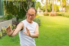 Azjatycki starszego mężczyzna odzieży koszula biały stojak i praktyki tai chi w kopii i parku apace Obraz Royalty Free
