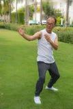 Azjatycki starszego mężczyzna odzieży koszula biały stojak i praktyki tai chi w parku Obrazy Stock