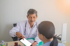 Azjatycki Starszego mężczyzny doktorski opowiadać żeński pacjent w lekarkach biurowych fotografia royalty free