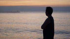Azjatycki starszy kobieta stojak wzdłuż główkowania przy wschód słońca morza sylwetką obraz royalty free