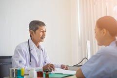 Azjatycki Starszy mężczyzna doktorski i cierpliwy obsiadanie opowiada w sali szpitalnej fotografia stock