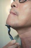 Azjatycki stary człowiek goli jego brodę Obrazy Royalty Free