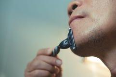 Azjatycki stary człowiek goli jego brodę Fotografia Stock
