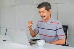 Azjatycki stary cz?owiek Raduje się, podnosi, pięści prawą rękę Siedzieć na krzesła spojrzeniu przy laptopu ekranem fotografia stock