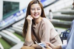 Azjatycki studencki opowiadać z jej przyjacielem Zdjęcie Royalty Free