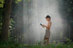 Azjatyckich uczni czytelnicze książki w Tajlandia wsi, Wiejski chil obraz stock