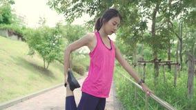 Azjatyckie atlet kobiety odziewa nogi grże jej ręki i rozciąga gotowy dla biegać na ulicie w miastowym miasto parku w sportach zdjęcie wideo