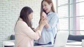 Azjatyckie biznesowe kobiety czuje szczęśliwe ręki podnosili odświętność po słuchają sukcesu Operacyjnego rezultat w biurze zbiory wideo
