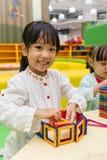 Azjatyckie Chińskie małe dziewczynki bawić się kolorowego magnesu klingerytu blok Zdjęcia Royalty Free