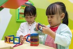 Azjatyckie Chińskie małe dziewczynki bawić się kolorowego magnesu klingerytu blok Zdjęcie Stock