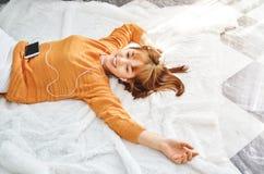 Azjatyckie kobiety jest ubranym pomarańczowe koszula, ono uśmiecha się i słucha muzyka, zdjęcie stock