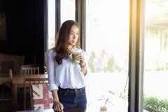 Azjatyckie kobiety piją kawowego i przyglądającego outside fotografia stock