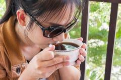 Azjatyckie kobiety pije gorącą kawę lub herbaty w świeżym szczęśliwym ranku li Zdjęcia Stock