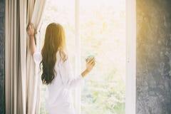 Azjatyckie kobiety pije kawę i budzili się w jej łóżku w pełni odpoczywającym fotografia stock