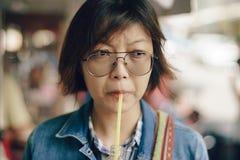 Azjatyckie kobiety pije sok pomarańczowego od butelki fotografia stock