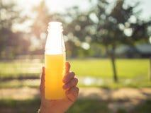 Azjatyckie kobiety trzyma sok pomarańczowy butelkę Zdjęcia Stock