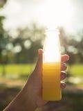Azjatyckie kobiety trzyma sok pomarańczowy butelkę Fotografia Royalty Free