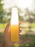 Azjatyckie kobiety trzyma sok pomarańczowy butelkę Fotografia Stock