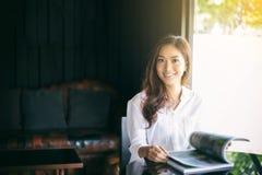 Azjatyckie kobiety uśmiecha się książkę dla relaksu i czyta przy kawą Fotografia Stock