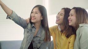 Azjatyckie kobiety używa smartphone sprawdza ogólnospołecznych środki w domu w żywym pokoju, grupa współlokatora przyjaciel ciesz zdjęcie wideo