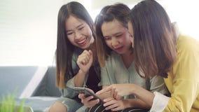 Azjatyckie kobiety używa smartphone sprawdza ogólnospołecznych środki w domu w żywym pokoju, grupa współlokatora przyjaciel ciesz zbiory wideo