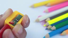 Azjatyckie kobiety używają ostrzarkę, używają dla ostrzyć błękitnego ołówkowego kolor na białej księgi tle Wybrana ostrość zbiory