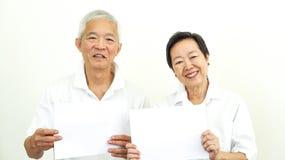 Azjatyckie starsze osoby dobierają się chwyta pustego miejsca znaka reklamę szczęśliwą polecają obraz stock