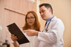 Azjatyckie Starsze samiec i kobiety lekarki trzyma schowek zdjęcia royalty free