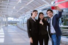 Azjatyckiego biznesmena i biznesowej kobiety uśmiech i brać selfie smartphone Zdjęcia Royalty Free