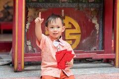 Azjatyckiego chłopiec chwyta czerwona koperta lub Pow Obraz Royalty Free