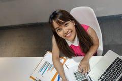 Azjatyckiego dumple biurowa dziewczyna z ładnym uśmiechem przy miejscem pracy obraz royalty free