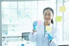Azjatyckiego kobieta naukowa kija kolorowa krótka notatka na desce obrazy stock