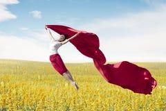 Azjatyckiego kobiety baleriny mienia czerwona tkanina robi dużemu skokowi na łące fotografia stock