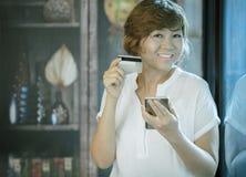 Azjatyckiego kobiety szczęścia twarzy mienia uśmiechnięty kredyt w ręce dla sh Obrazy Royalty Free