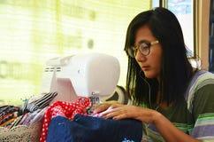 Azjatyckiego kobiety use maszynowy szyć odziewa Obraz Royalty Free