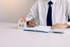 Azjatyckiego mężczyzny podpisywania papieru kontraktacyjna zgoda dla domu z modelem zdjęcie stock