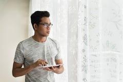 Azjatyckiego nastoletniego mienia cyfrowa pastylka podczas gdy patrzejący outside jego mieszkanie fotografia stock