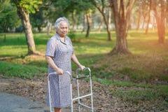 Azjatyckiego seniora lub starszej starej damy kobiety cierpliwy spacer z piechurem w parku obrazy royalty free