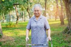 Azjatyckiego seniora lub starszej starej damy kobiety cierpliwy spacer z piechurem w parku obraz royalty free