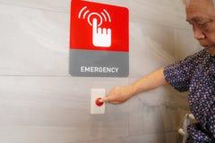 Azjatyckiego seniora lub starszej starej damy kobiety pacjenta prasy przeciwawaryjny guzik w specjalnej toaletowej łazience dla k zdjęcia royalty free