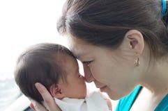Azjatyckiego uśmiechniętego kobiety mienia dziecięcy dziecko w jej rękach, szczęśliwy macierzyństwo obraz royalty free