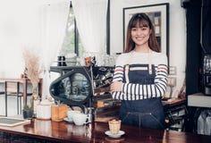 Azjatyckiej żeńskiej barista odzieży cajgowy fartuch krzyżował jej ręki przy kontuarem obrazy stock