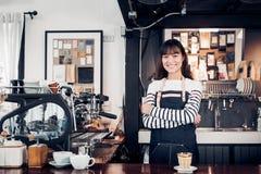 Azjatyckiej żeńskiej barista odzieży cajgowy fartuch krzyżował jej ręki przy kontuarem zdjęcie royalty free