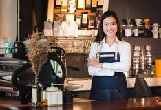 Azjatyckiej żeńskiej barista odzieży cajgowy fartuch krzyżował jej ręki przy kontuarem obraz stock