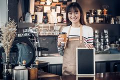 Azjatyckiej żeńskiej barista odzieży cajgowy fartuch trzyma filiżankę, blan i obraz stock